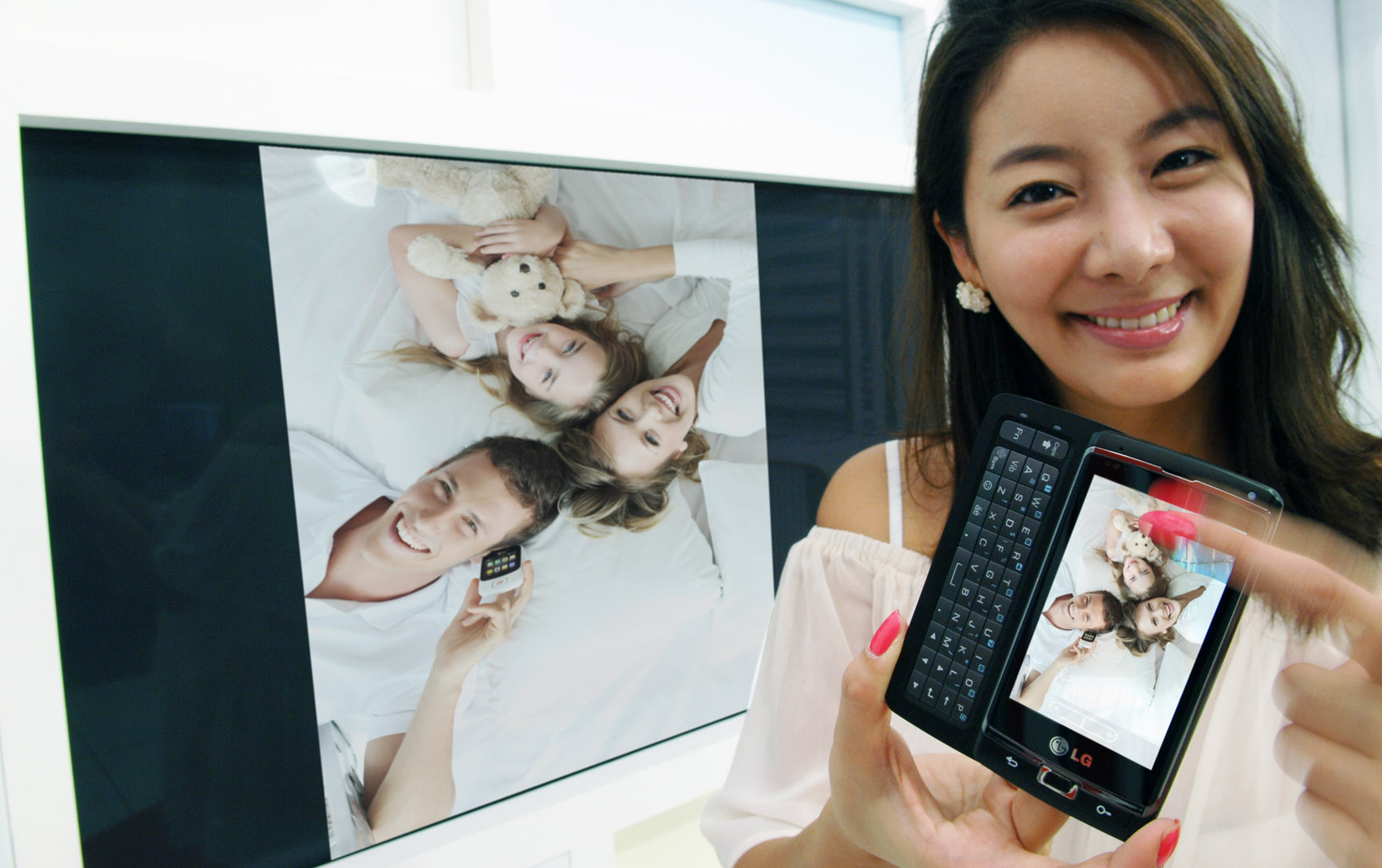 A female model is showing a family photograph on the TV by using LG's unique multimedia sharing technology on her LG Optimus 7.