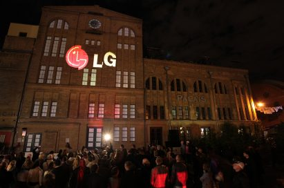 A large audience observes a gigantic 3D LG logo projected onto the front of a building in Kulturbrauerei, Berlin