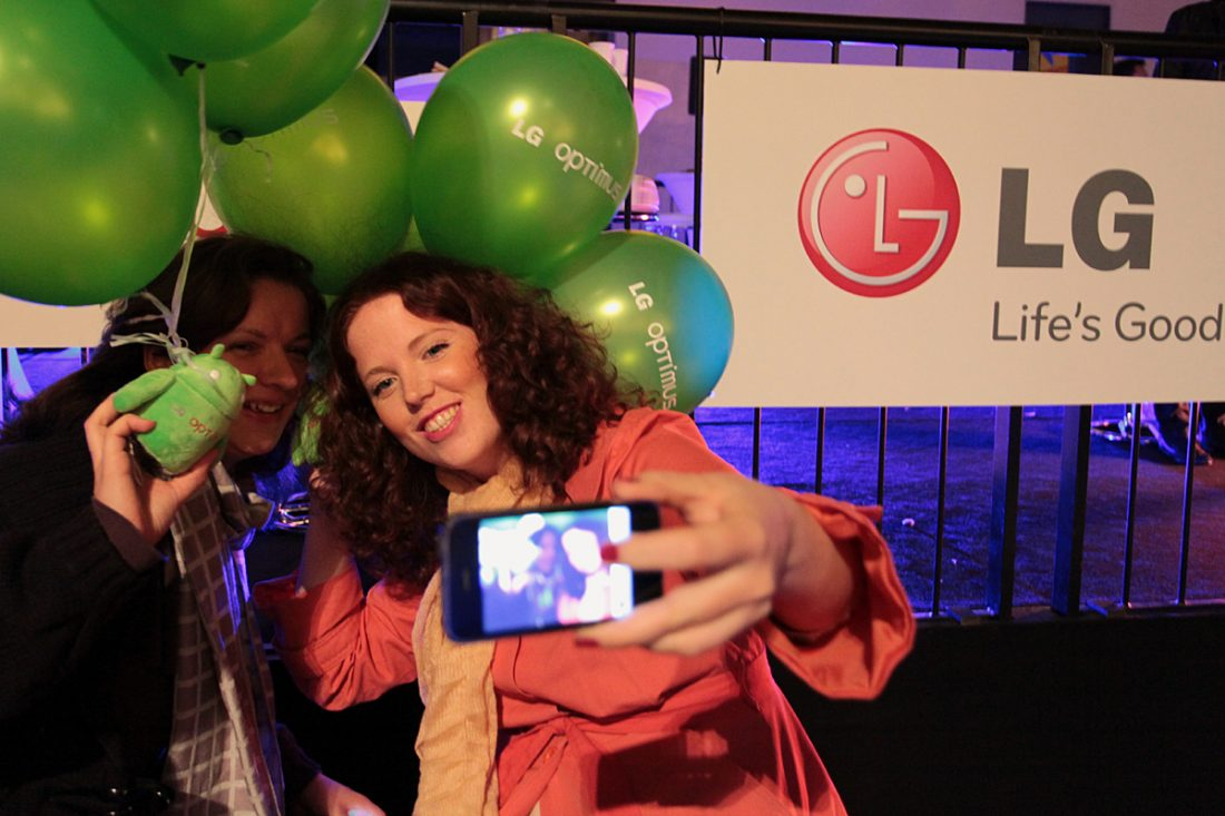Two attendees take a selfie with an android doll and LG Optimus One balloons, while leaving the event.