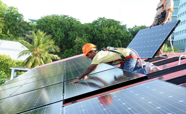 Mohamed Nasheed, president of the Maldives, helps install a solar panel on the president's official residence, Mulee Aage Palace.