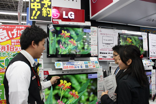 A man explains LG's LED LCD TVs to two visitors at an LG store booth set up in Japan.