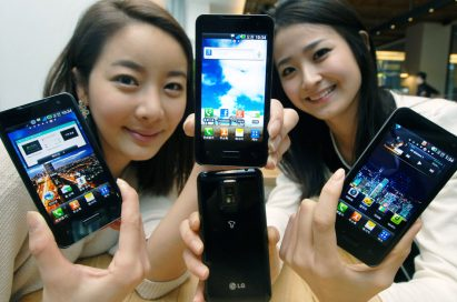Two models hold up four models of the LG Optimus 2X displaying both its front and back at the smartphone's launch event.
