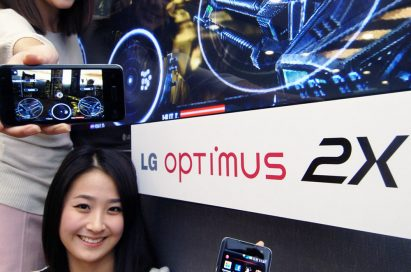 Two models pose with three LG Optimus 2X smartphones next to an LG TV showcasing the phone's gaming potential.