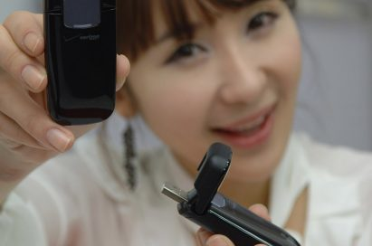 A model holds two LG Verizon Wireless LTE USB Modems, while demonstrating how the lid opens and closes