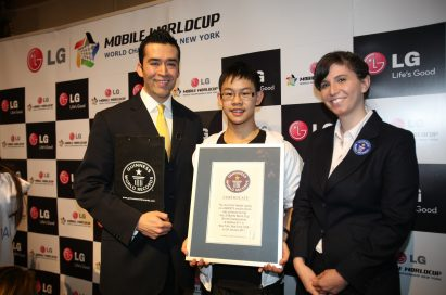 Cheong Kit Au from Australia, who set the Guinness World Record® for the fastest texting recorded on a QWERTY mobile phone device, poses with representatives of the Guinness World Records while holding his certificate