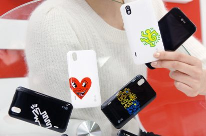 A model holds up two LG Optimus Black phones, showing off the front and rear of the device while next to 6 different back cover designs from the Keith Haring Foundation