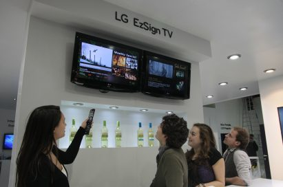 A woman demonstrating the LG EzSign TV to three visitors at ISE 2011