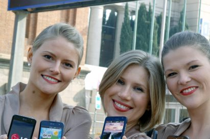 Three female models hold LG Optimus 3D, LG Optimus 2X and LG Optimus Black and show its front views at MWC 2011 event venue
