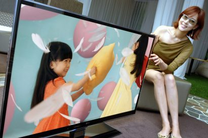 A female model wearing 3D glasses tries to touch the screen of LG's LW980S 3D LCD TV while the TV displays little girls playing a pillow fight.