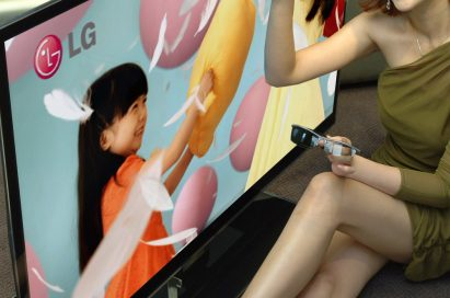 A female model points at the screen of LG's LW980S 3D LCD TV with 3D glasses in her hand.