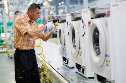 A male worker assembling the compartments of washing machines at an LG factory