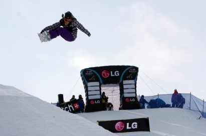 A snowboarder jumps above the LG Electronics stands