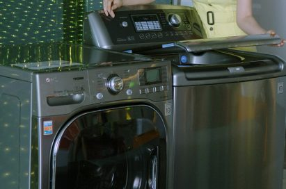 A side view of a woman posing with the LG top-load and front-load washing machines while slightly opening the door of top-loader