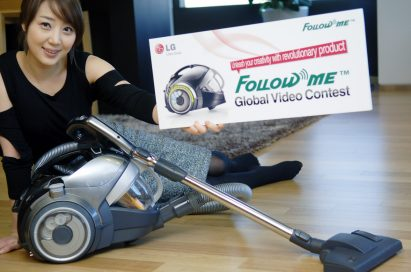 A woman sitting on the floor while posing with the banner of 'Follow Me Global Video Contest' in front of the LG KOMPRESSOR FOLLOW ME™ vacuum cleaner