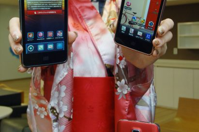 A woman in traditional Japanese clothing holds up two LG Optimus LTEs and shows its front view and LG Optimus LTE showing rear view is displayed in front of her