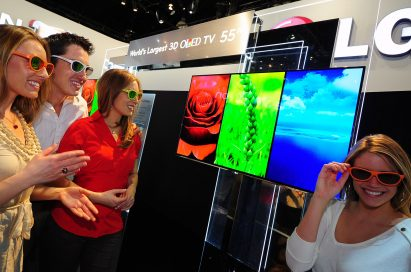 Three visitors and a model wearing 3D glasses to experience LG's 3D TVs at CES 2012