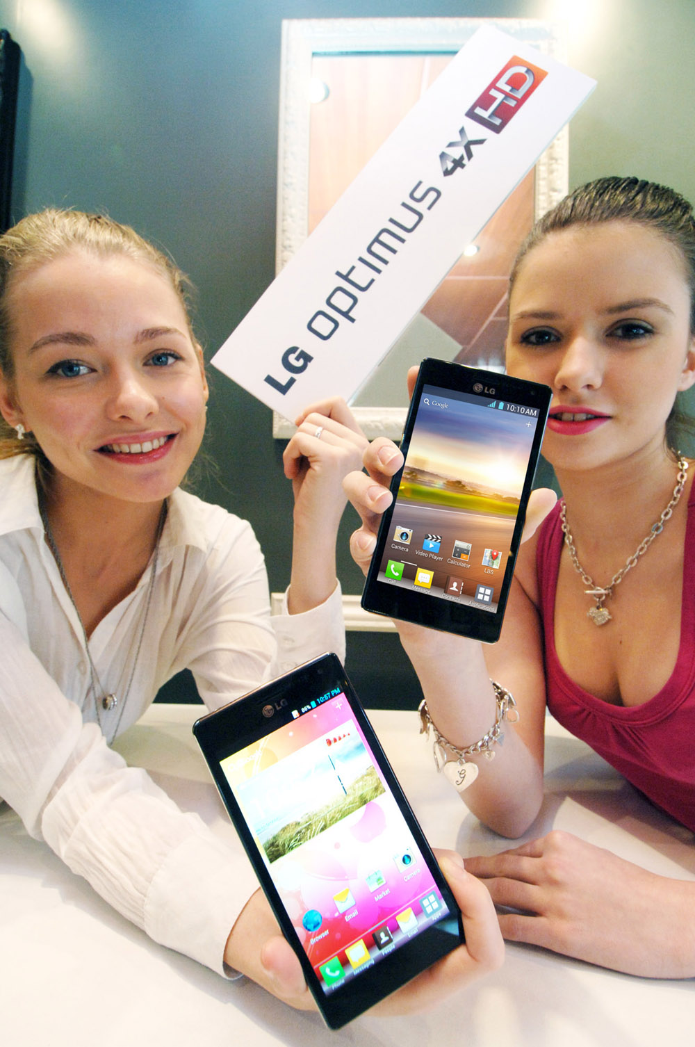 Two models holding up two LG QUAD-CORE smartphones and a promotional panel engraved with the brand name LG OPTMUS 4X HD