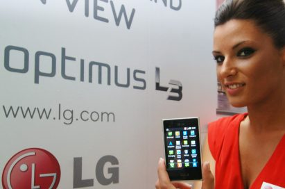A female model holds two LG Optimus L3s and shows its front views in front of LG Optimus L3 advertisement panel