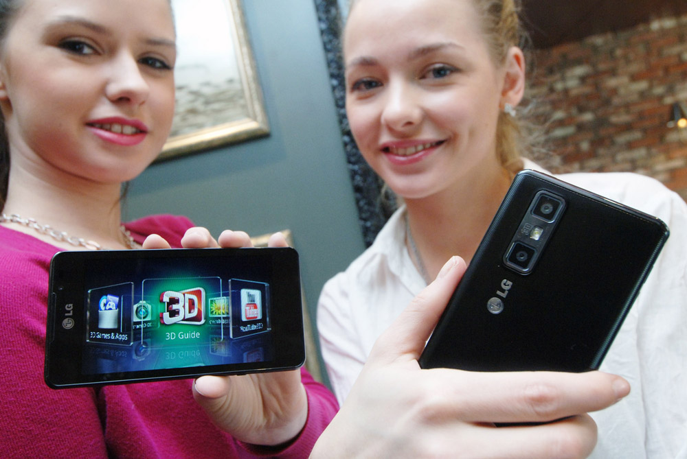 Two female models hold up LG's Optimus 3D Max at its launch event.