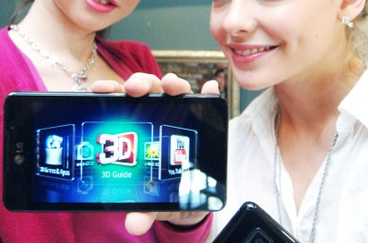 Two female models hold LG Optimus 3D Max and show its front and rear views