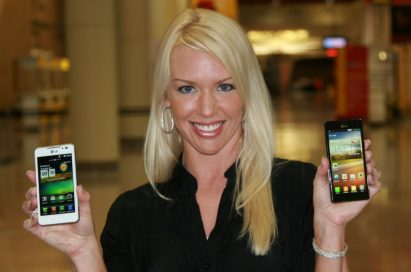 A female model holds white and black LG smartphones and shows its front views