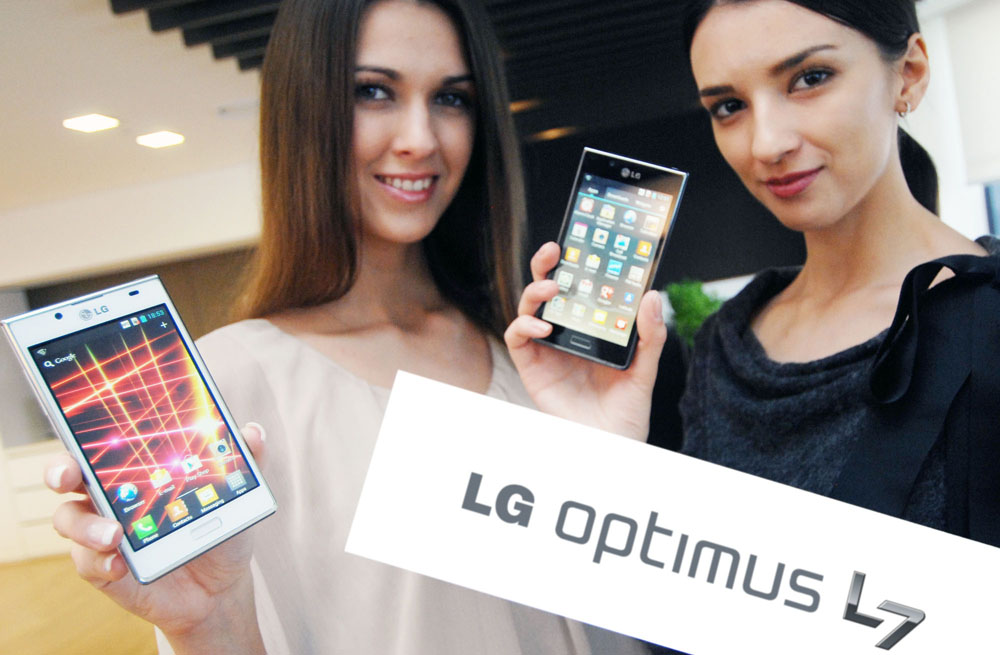 Two female models hold the LG OPTIMUS L7 smartphone and its brand name panel at the launch event.
