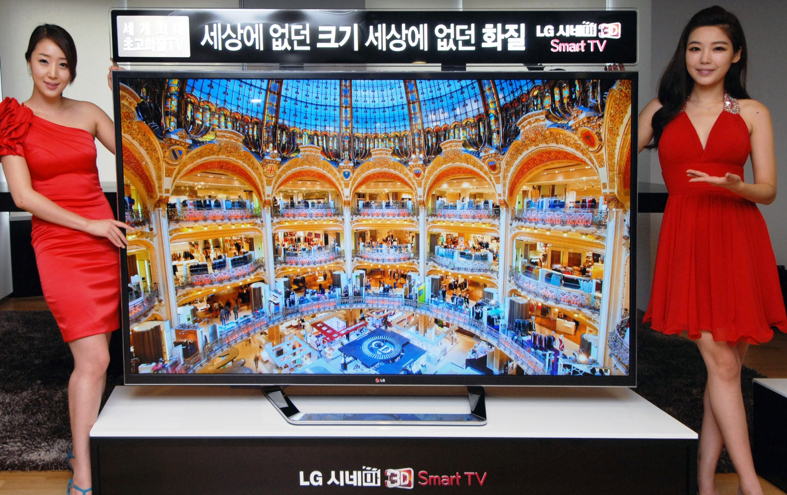 Two models posing at either side of the world's first 84-inch Ultra Definition 3D TV by LG