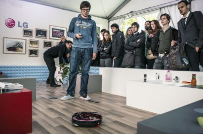 A man controlling LG HOM-BOT with its remote control in front of many visitors
