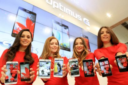 Four female models are smiling at a camera holding various strategic Optimus series devices at MWC 2013 - G, Vu:, F and LII.