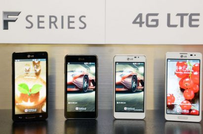 "Four of new LG Optimus F series smartphones are displayed. From left to right; Optimus F7 in black color, Optimus F5 in black color, Optimus F5 in white color, Optimus F7 in white color. A panel saying ""F SERIES 4G LTE"" is also attached to the wall behind the handsets."