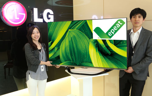 Two LG employees holding up an LG TV displaying the EPEAT logo.