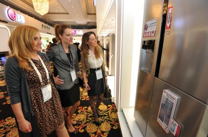 Three visitors observe an LG refrigerator with the Door-in-Door feature