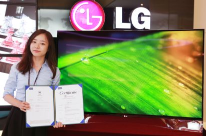 An LG representative holds up the green certificate given by three certification bodies, including Intertek, the European Commission and the Electronic Product Environmental Assessment Tool, while standing in front of LG's Curved OLED TV