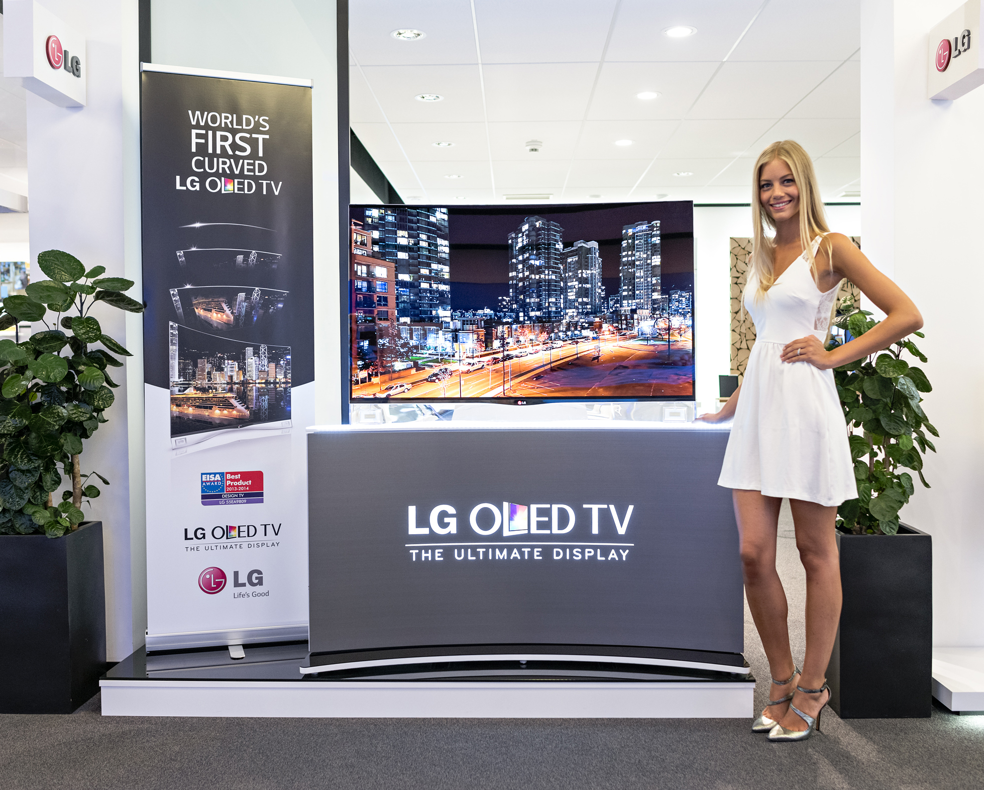 A model is demonstrating LG CURVED OLED TV model 55EA9800