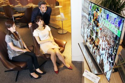 Travelers admiring the LG 55-inch OLED TV's incredible display in an airport lounge