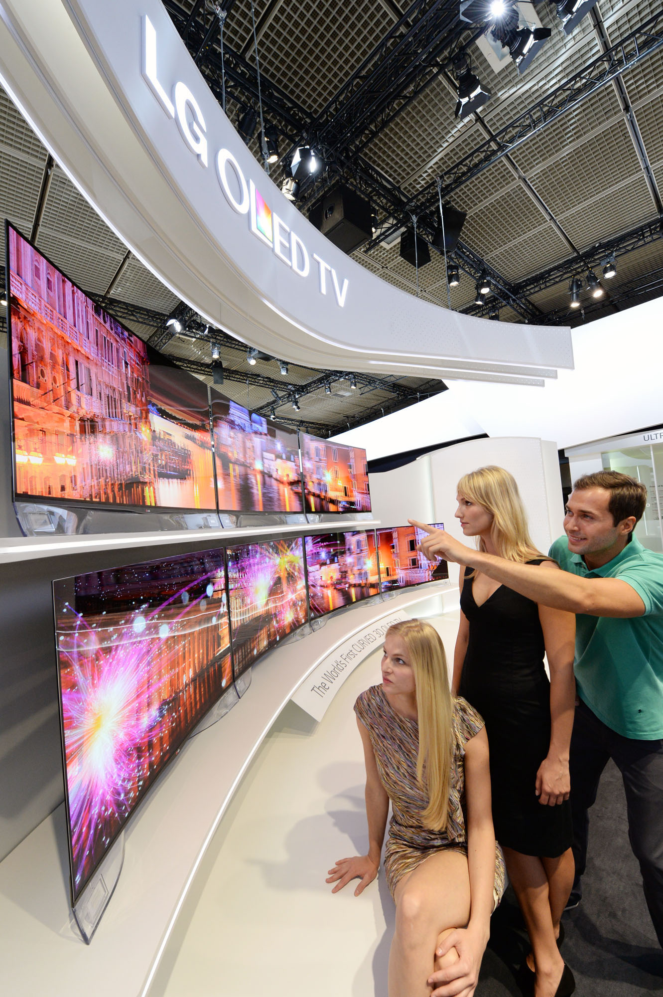 Three visitors view two rows of LG's CURVED OLED TVs on show at IFA 2013