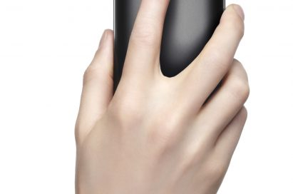 A person's hand using the rear fingerprint sensor on the back of the LG G2.