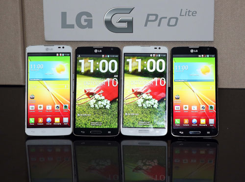 "Front views of four LG G Pro Lites displayed upright on a table, with an "" LG G Pro Lite"" logo attached to the wall behind."