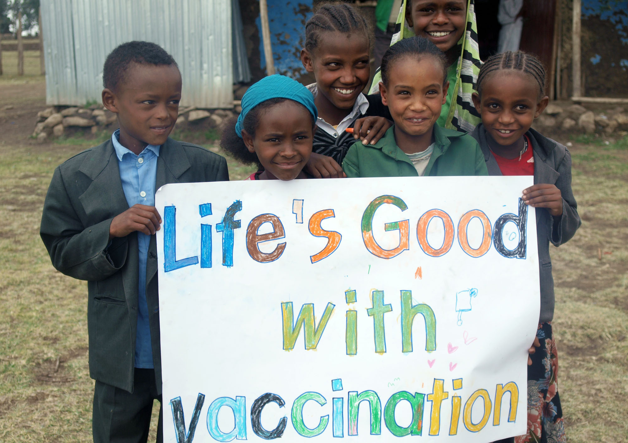 "Children hold a ""Life's Good with vaccination"" sign together with smiles."