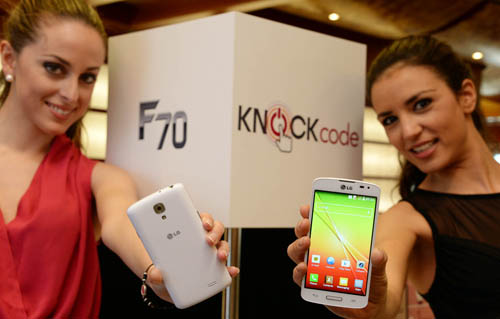 From left to right; A female model is holding a LG F70 in white color to show its back and another model is trying to show its front.
