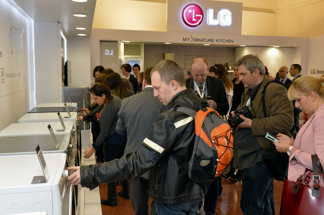Visitors touching and looking around LG's washing machines at LG Innovative Festival Europe