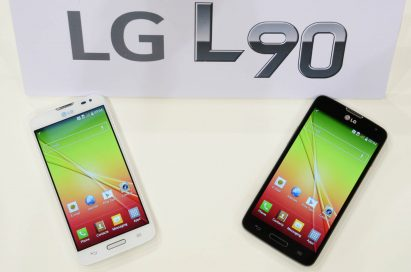 Two LG L90s, each in white and black color, are lying on a table and a panel with the logo of LG L90 on is standing on the table.