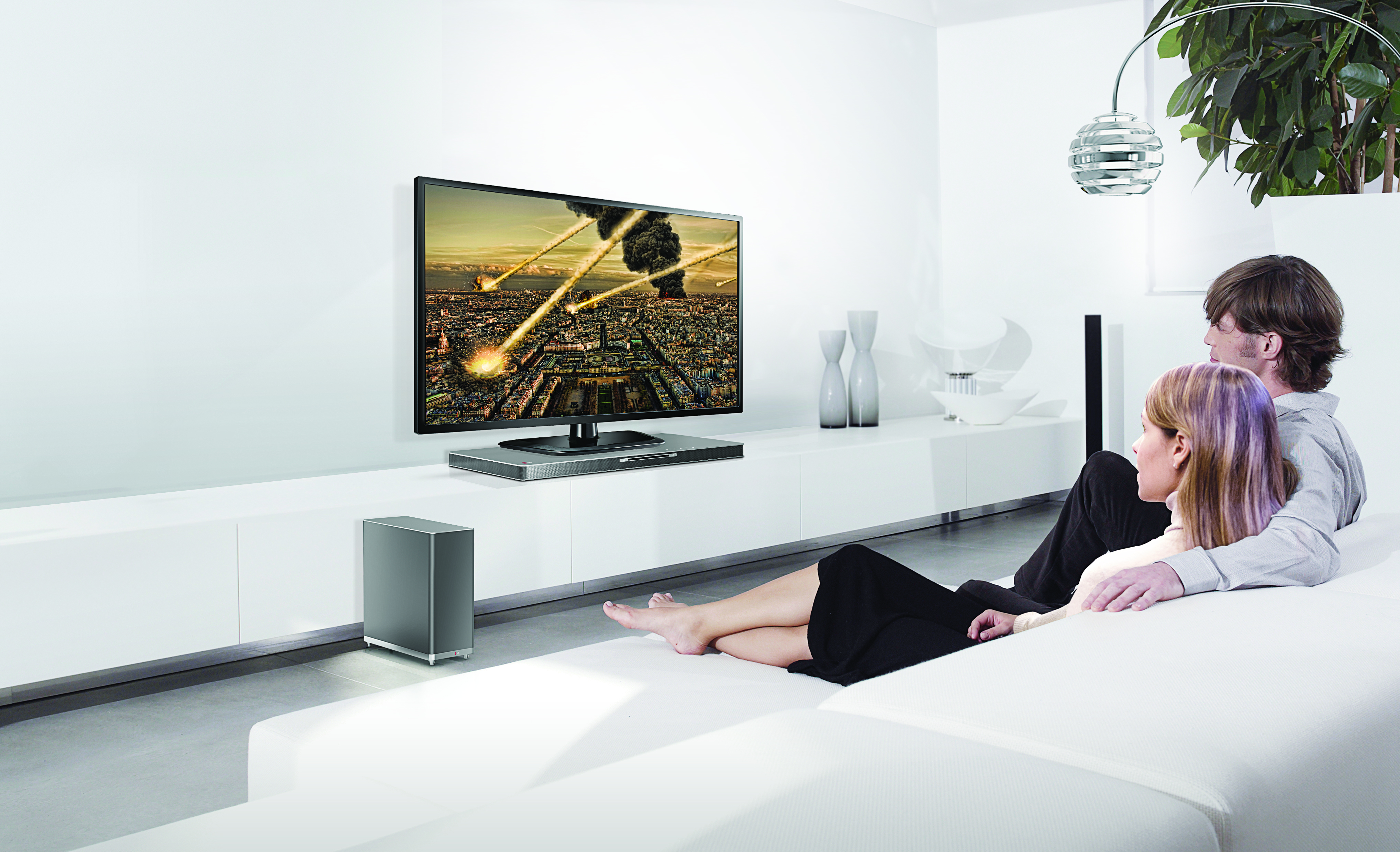 Two models watching TV on the LG SoundPlate model LAB540 while enjoying an impressive sound experience