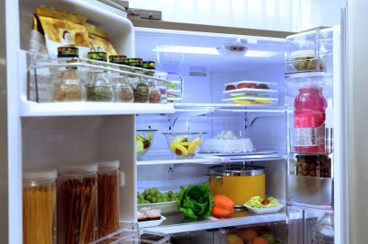 Inside LG's smart refrigerator with Smart View camera, which is located on the interior's ceiling. The refrigerator is full of various food including bottles of spices, fruits, vegetable and beverages.