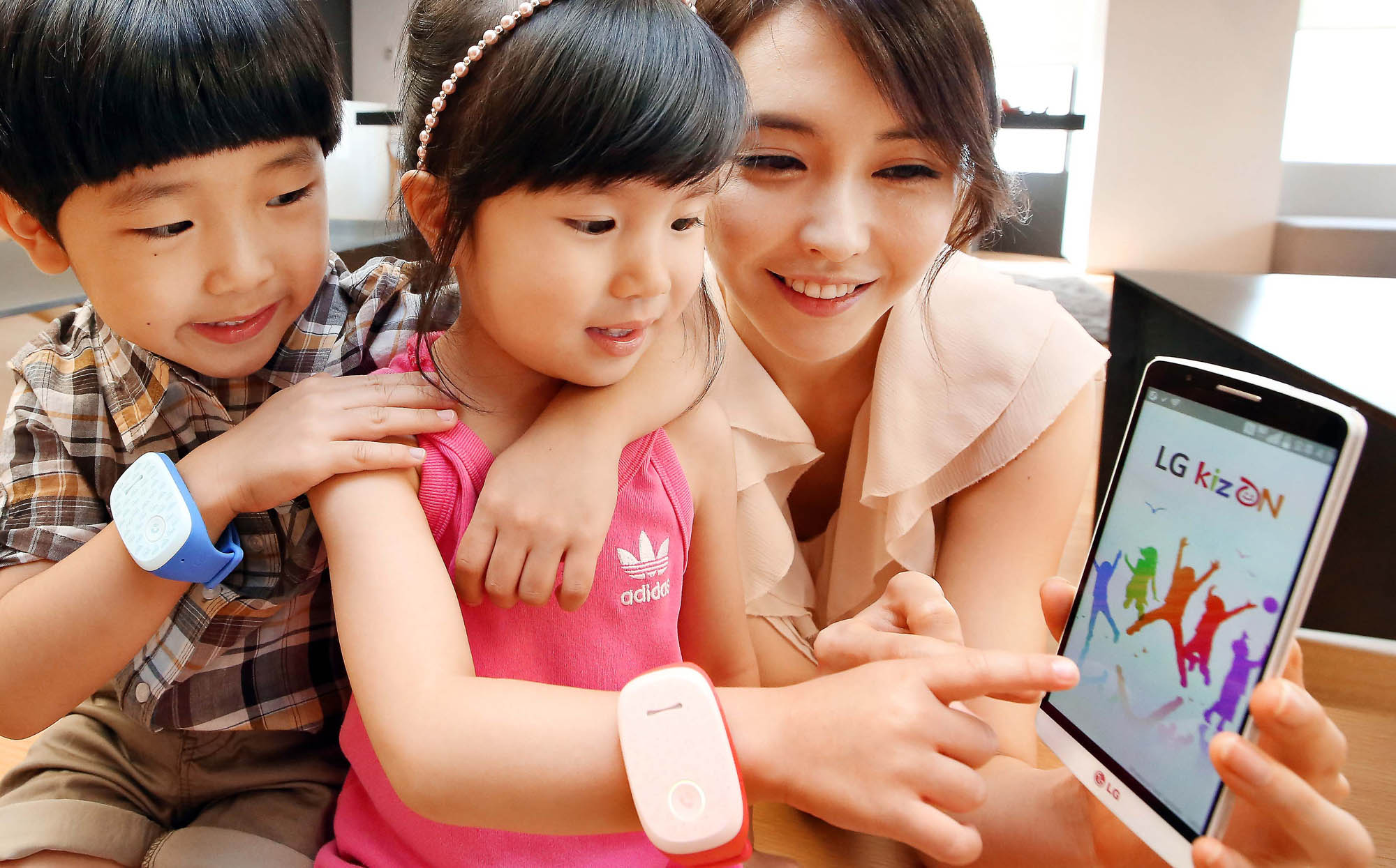 Two kid models wearing LG KizONS and a female model are trying to link the handsets with LG G3