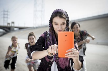 A woman and 3 kids are taking selfies with a LG G Pad 8.0 LTE.