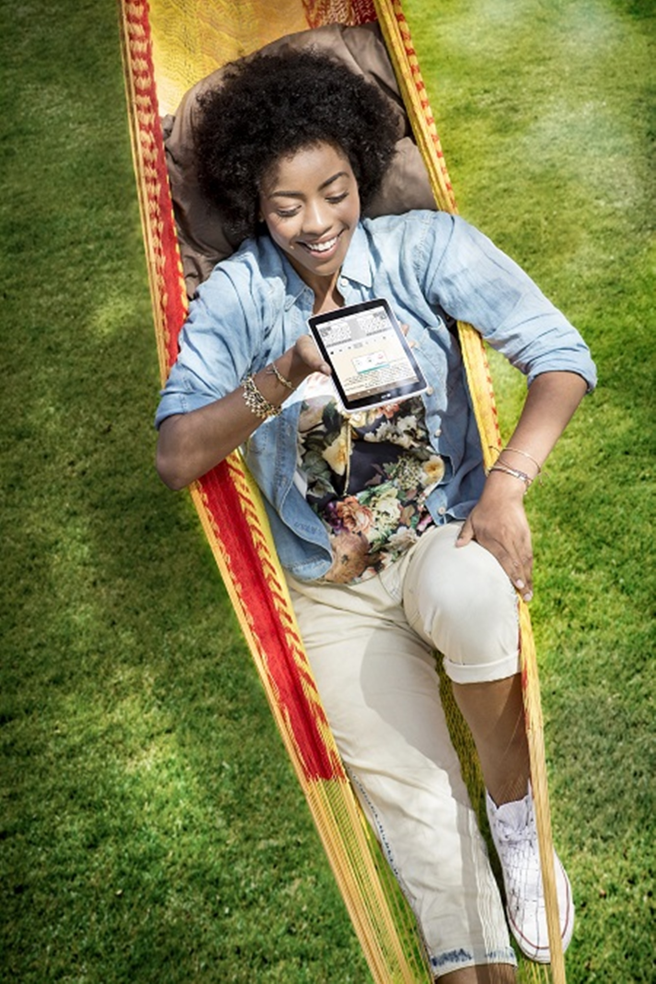 A girl is lying on a hammock holding a LG G Pad 8.0 LTE with her right hand.