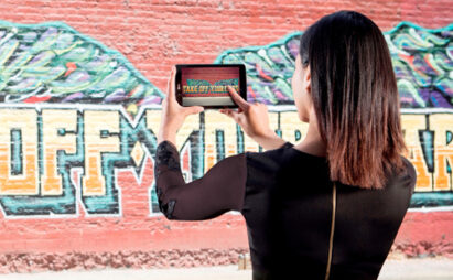 A woman is taking a picture of graffiti with LG G Pad 8.0 LTE