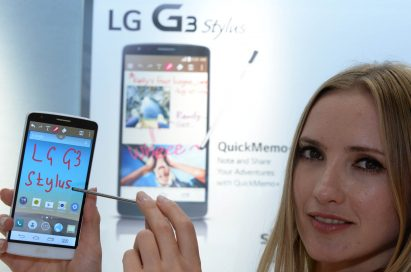 """A model showing off the LG G3 Stylus' screen by writing """"LG G3 Stylus"""" with the QuickMemo function."""