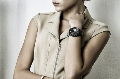 A woman is leaning on her elbow wearing a LG G Watch R.